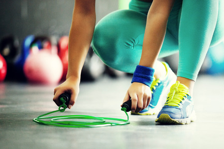 62772856 - young fit woman is taking jumping rope. close up.